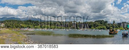 Pucon, Chile-january 31, 2020: Boats On The Shore Of Lake Villarrica With The Volcano Of The Same Na
