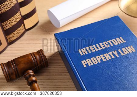 Intellectual Property Law Book And Judge's Gavel On Wooden Table