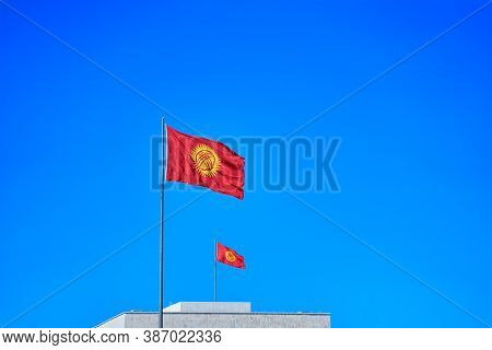 Two Kyrgyzstan Flags Waving In The Wind Against Blue Sky Together. Diplomacy Concept, International