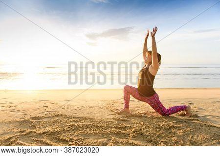 Woman Yoga On The Beach