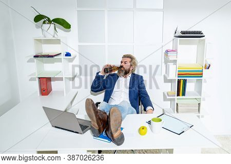 Bored Drunk Businessman In Office At End Of The Work Day. Drunk Business Man With A Bottle Of Alcoho
