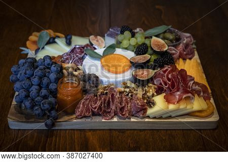 Food Board With Cured Meats Prosciutto, Salami And Coppa, Hard And Soft Cheeses Brie, Cheddar, Gouda