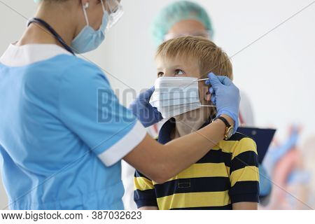 Boy Is Put On Protective Medical Mask In Doctors Office. Child Health Safety In Pandemic Concept