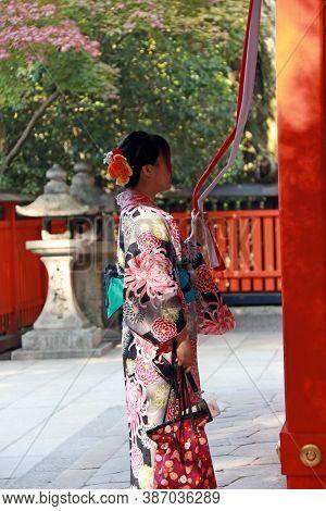Fushimi-ku, Kyoto, Japan, November 17, 2017 : Woman In Kimono Dress To Ringing The Bell For Bless At