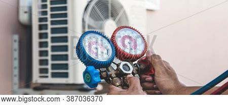 Air Repair Mechanic Using Measuring Pressure Gauge Equipment For Filling Home Air Conditioner After