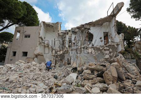 Man Kneels In Front Of Broken House On Ruin Demolishing Site After Destruction.