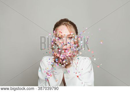 Young Happy Woman Blowing Colorful Confetti On Gray Banner Background