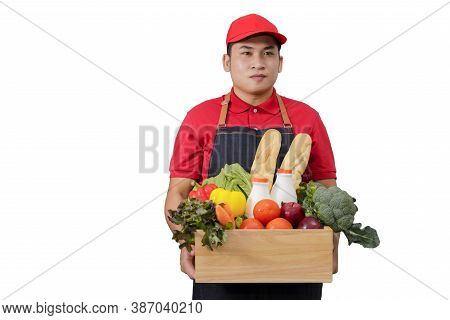 Grocery Delivery Courier Man In Red Uniform With Grocery Box With Food, Fresh Fruit And Vegetable. D