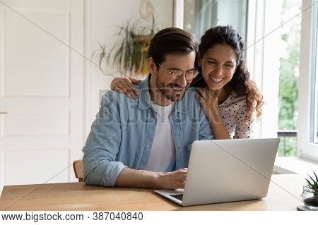 Happy Couple Use Modern Laptop At Home Together