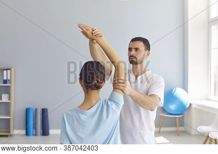 Young Male Osteopath Masseur In White Clothes Kneads The Joints Of The Girls Hand.