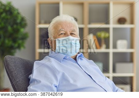Serious Senior Citizen Wearing Medical Face Mask Sitting In Armchair Looking At Camera