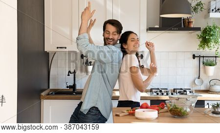 Overjoyed Couple Tenants Dance In Kitchen Cooking Together