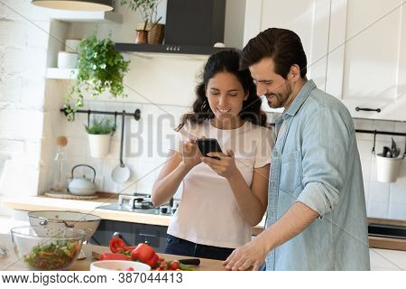 Happy Couple Tenants Cooking At Home Using Cellphone