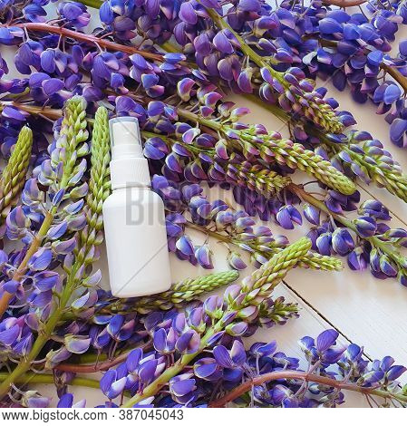 Mockup Of Unbranded White Plastic Spray Bottle And Lupine Flowers On White Wooden Background. Natura
