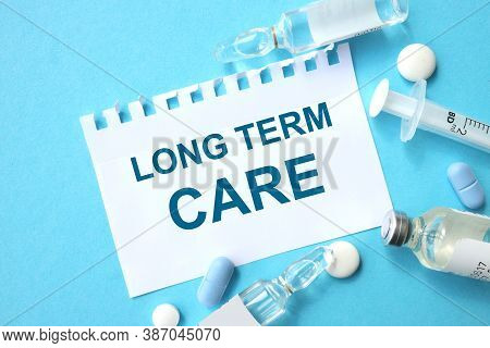 Long-term Care. Text On A Blue Background Near The Syringe And Ampoules