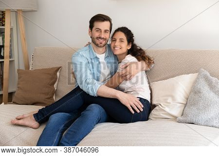 Portrait Of Smiling Couple Renters Relax On Couch