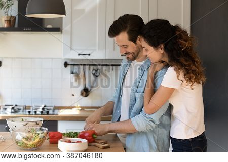 Happy Couple Tenants Cooking Together In Morning At Home