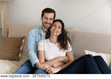 Portrait Of Happy Couple Renters Relax On Couch