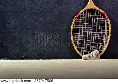 Vintage Badminton Racket On A Black Background. Badminton Racket On Plywood. Racket And Shuttlecock