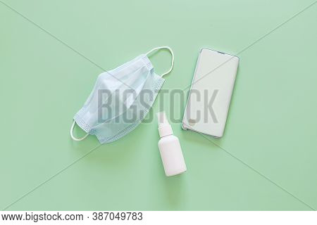 Top View Of Blue Surgical Protective Mask, Smartphone And Liquid Antimicrobial Spray - Mockup Of Unb