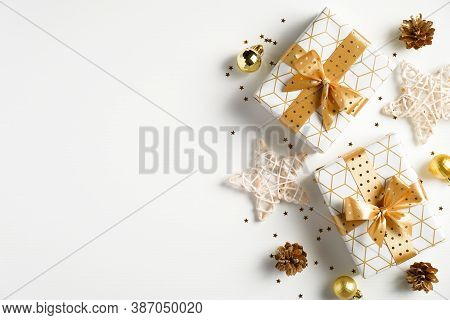 Christmas Flat Lay Composition. Christmas Golden Decorations, Gift Boxes, Stars, Confetti On White B