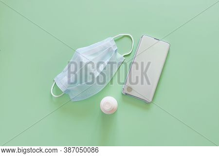 Top View Of Blue Surgical Protective Mask, Smartphone And Liquid Antimicrobial Spray On A Light Gree