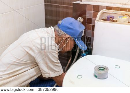 Asian Elderly Plumber Repairing Broken Water Pipes In Bathroom, Worker, Builder, Repairman With Tool