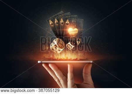 Creative Background, Online Casino, In A Man's Hand A Smartphone With Playing Cards, Roulette And Ch