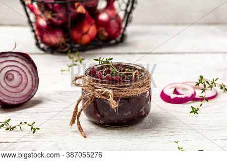 Red Onion Marmalade Jam Confiture In Jar. Vegetable Jam On White Wooden Background. Delicious Sauce.