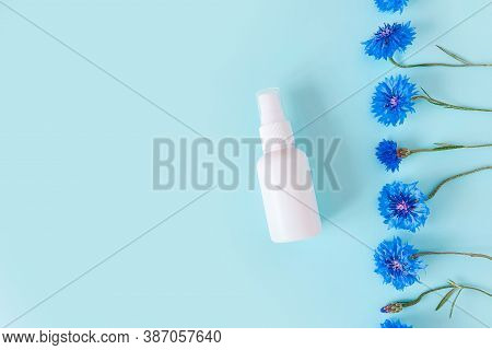 Top View And Close-up Of Unbranded White Plastic Spray Bottle Mockup And Flower Line Of Blue Cornflo