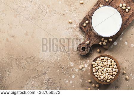 Soy Milk And Soy Bean On Beige Background. Alternative Non-dairy Milk Concept. Vegan Beverage. Copy