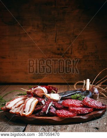 Meat Appetizer Platter With Bacon, Smoked Sausage And Salami On A Wooden Cutting Board, Selective Fo