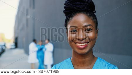 Portrait Of African American Young Beautiful Woman Doctor Looking At Camera And Smiling Cheerfully.