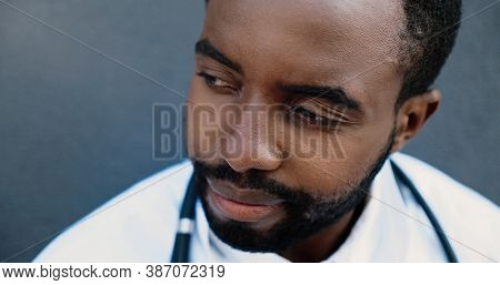 Tired Young Sad African American Man Doctor Taking Off Medical Mask And Resting While Leaning On Wal