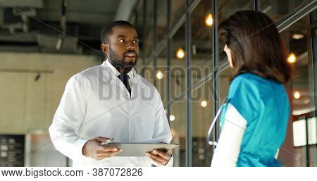 Mixed-races Male And Female Doctors Talking Cheerfully In Clinic. Multi Ethnic Man And Woman, Medics