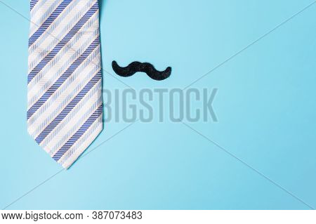 Blue Neckties And Mustache On Blue Background. Happy Father's Day And International Men's Day Concep