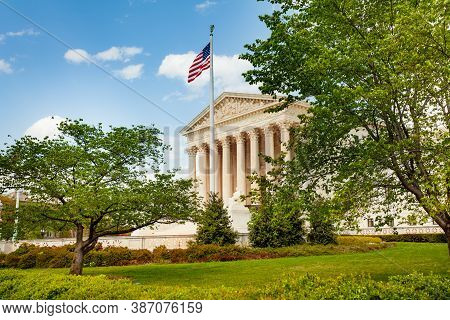 Supreme Court Of The United States Building With Us Flag Over Sky