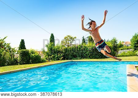 Teenage Boy Jump In Mid Air Into The Swimming Pool View From Side Scream And Smile With Hands Up In