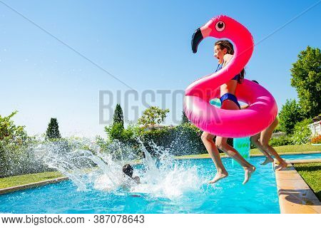 Happy Little Teenage Girl Holding Inflatable Rose Flamingo Jump In Mid Air To Swimming Pool With Fri