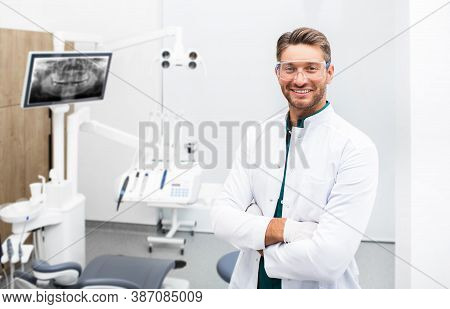 Confident Male Dentist Standing In His Modern Clinic. Dental Hygienist Wearing Protective Glasses Sm
