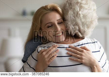 Loving Affectionate Millennial Daughter Holding In Arms Middle Aged Mother