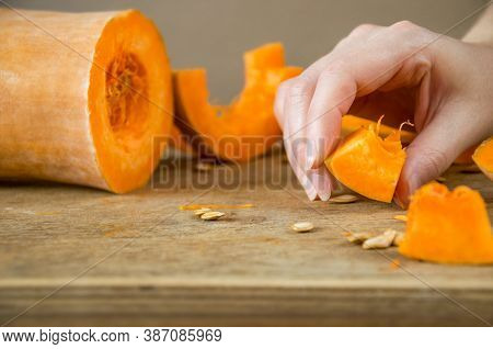 The Chef's Hand Is Holding A Slice Of Pumpkin. Small Slices Of Fresh Pumpkin On The Table While Maki