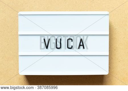 Lightbox With Word Vuca (abbreviation Of Volatility, Uncertainty, Complexity And Ambiguity) On Wood