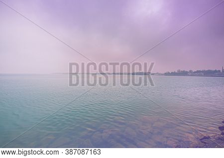 Deserted Shore Of Lake Garda In Italy In The Absence Of Tourism In Faded Color Effect.