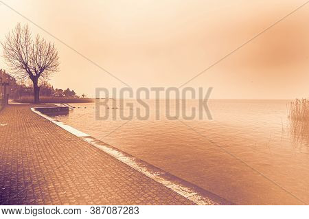 Deserted Shore Of Lake Garda In Italy In The Absence Of Tourism At Dawn In A Contemporary Style.