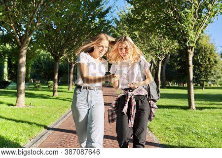Two Happy Talking Walking Teenage Girls Looking At Smartphone Screen, College Students Walking In Pa