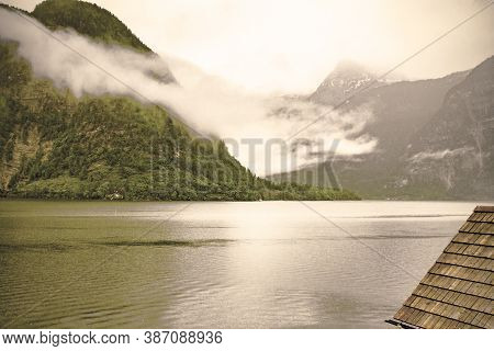 Rain And Clouds On The Hallstattersee In Austria. Morning Mist Over The Austrian Landscape With Lake