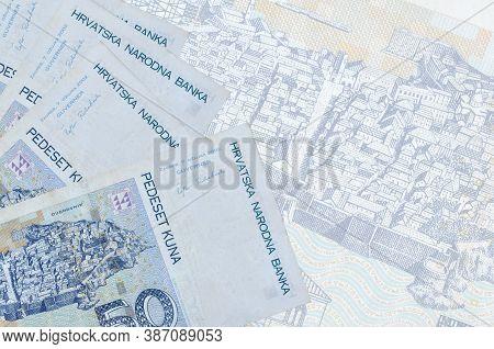 50 Croatian Kuna Bills Lies In Stack On Background Of Big Semi-transparent Banknote. Abstract Busine