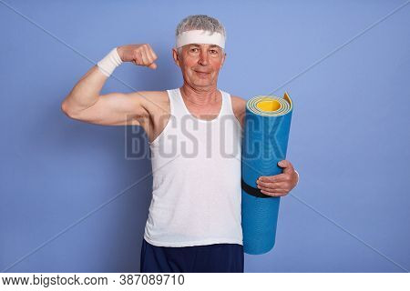 Energetic Senior Man Has Physical Training, Holding Yoga Mat, Showing Biceps And His Power, Looking