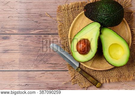 Avocado Half On Wood Plate On Wood Background And Copy Space. Ripe Fresh Green Avocado